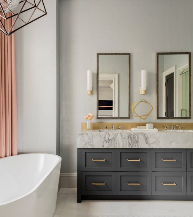 White marble countertops and gold accents make this bathroom by elms interior design right on trend